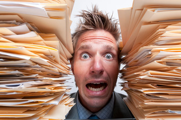 Stressed office worker screaming for help from between two massive stacks of file folders
