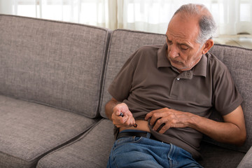 Senior man taking an insulin injection on his own. (Health and fitness)