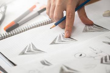Graphic designer drawing sketches logo design.
