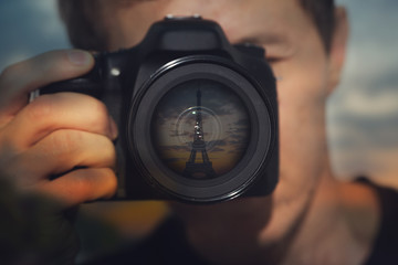 image of a young man with a camera. The lens reflects the Eiffel tower on the background of the sunset. Theme of  photography, travel, vacation, trip.