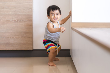 Cute active asian little baby boy is standing on the floor and trying begin to walk for first step himself, concept of learning and developing of child in the first year of life. Fotobehang