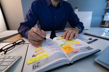 Fototapete - Businessman Making Agenda On Personal Organizer