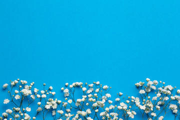 Foto auf Leinwand Blumen Floral composition with light small white gypsophila flowers on deep blue background, top view, frame, background