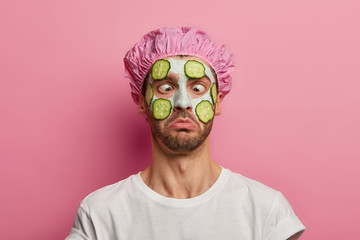Young man crosses eyes, applies cream mask on face with cucumber, has beauty session, wears bath cap, reduces dark dotes on complexion, isolated over pink background. Facial treatment concept Fotobehang