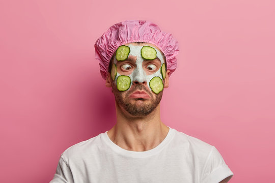 Young man crosses eyes, applies cream mask on face with cucumber, has beauty session, wears bath cap, reduces dark dotes on complexion, isolated over pink background. Facial treatment concept