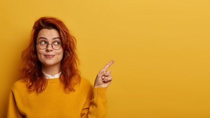 Photo of lovely ginger woman points index finger aside, demonstrates promo on right, looks with interesting expression, has wavy red hair, presents promo, recommends advertisement over yellow wall.