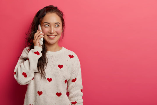 Smiling pretty mixed race female talks on cellphone, discusses what happened during day with mother, has happy look, wears white jumper, enjoys leisure tinme, stands indoor over pink studio wall