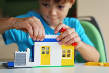 Junge baut mit Bausteinen ein Haus