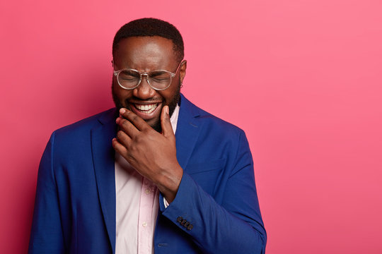 Photo of overjoyed Afro American man laughs at funny story, cant stop giggling, has white teeth, thick beard, wears formal suit, squints face, isolated on pink background, glad to achieve success