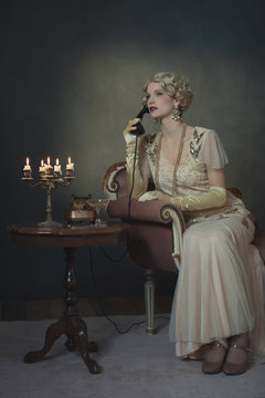 Retro 1920s fashion woman on the phone while sitting on sofa beside table with candlestick and glass of champagne.