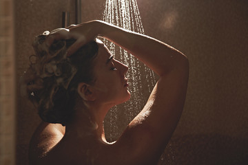 Beautiful satisfied European woman washes away shampoo from the head hair in bathroom, takes a shower and enjoys, smiling..