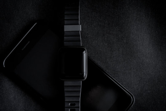 Wearable sports technology, smart watch screen with phone to track fitness on black