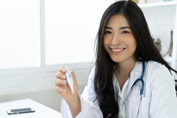Asian Female doctor in medical uniform, stethoscope holding digital clinical thermometer of high fever temperature. Healthcare personnel,medicine health care cold flu fever examination disease concept