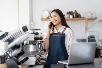 Happy Asian woman barista working on laptop smiling and talking on smartphone, accepting writing order at a coffee shop. waitress in Cafeteria Small business owner, online purchase and service concept