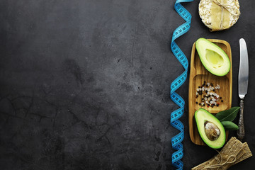 Avocado cooking recipes. Ripe green avocado on a wooden cutting board for serving.