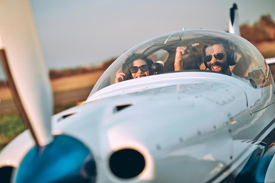 Young woman and pilot in in the cockpit of a plane