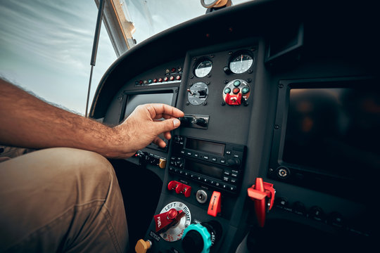 Pilot inside a cockpit small airplane. Pilots hand on the controls