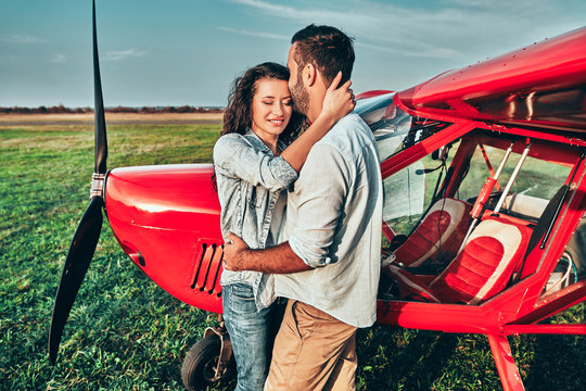Beautiful romantic couple is standing near private plane in airfield