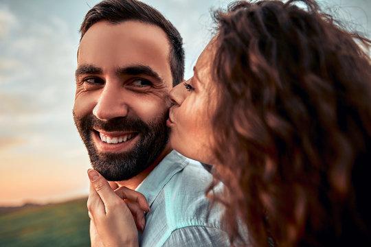 Pretty woman kissing man on the cheek