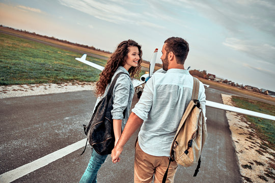 Happy young couple walking from a private air plane walking on runway with backpacks.