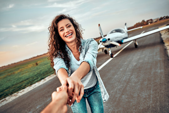 Happy young woman wants to fly in a small aircraft holding boyfriend's hand.