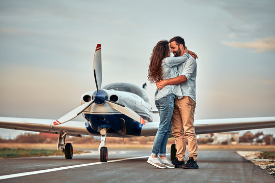 Stylish couple standing near a plane at the airport.
