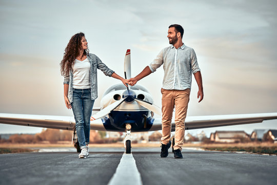 Full-length image of beautiful young stylish couple near private plane.