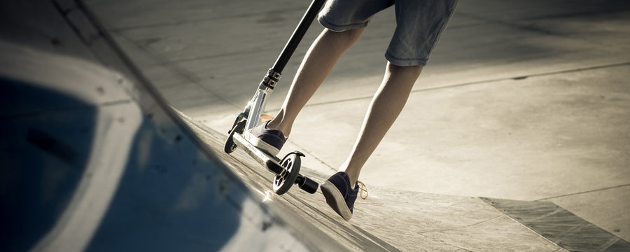 Close up view of tennager's feet riding a scooter making tricks on half pipe. Trendy young skater enjoying outdoors at the skatepark with kick scooter. Youth, freedom, sport joy and carefree concept