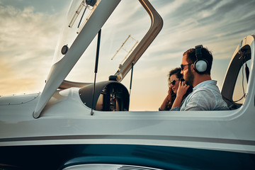 Two people sit into ultralight propeller-driven airplane and get ready for taking off