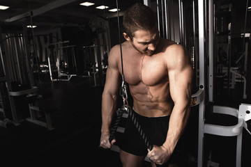 Portrait of fitness athlete man with muscular body does exercises on sports equipment in the gym,...