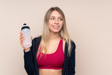 Young sport blonde woman over isolated background with sports water bottle