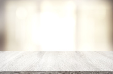 image of wooden table in front of abstract blurred window light background