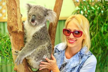 Garden Poster Koala Happy caucasian woman touches a koala bear, Phascolarctos cinereus, on eucalyptus trunk in Victoria. Encounter with Australian marsupial animal in Australia. koala is an arboreal herbivorous marsupial