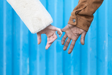 Arms of interracial couple holding hands, great love symbolic concept, blue background.