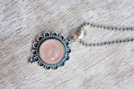 Silver pendant on neutral bright wooden background