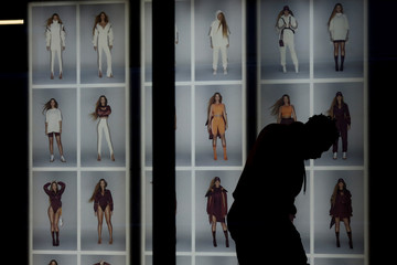 A shopper stands next to images of pop star Beyonce at an Adidas store on Oxford Street in London
