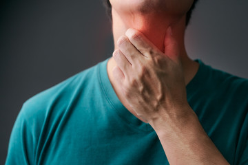 Unhappy asian man using his hand touching on his neck Suffering From Gland Inflammation.Adult man feel bad on sore throat and sick from cold, flu.Throat pain, sickness, healthcare and medical concept.