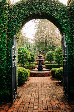 Outdoor Green secret garden with arched entry and gate and a fountain in the middle and red brick and black iron gate