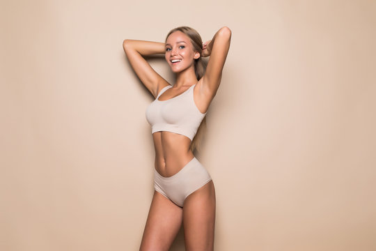 Young woman in underwear on beige background. Fitness, diet, skin and body care