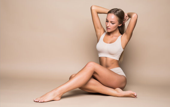 Young pretty woman sitting on the floor in underwear isolated on beige background
