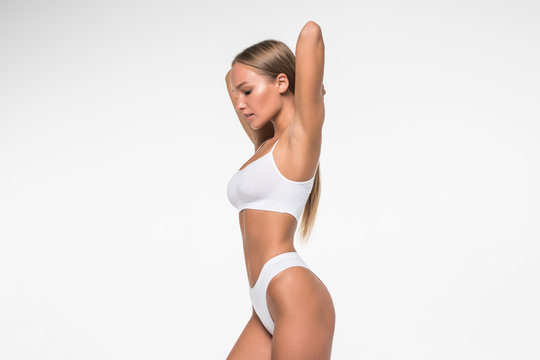 Muscular woman's body in white lingerie isolated on white background
