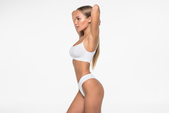 Young woman with beautiful slim perfect body in white bikini isolated white background