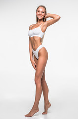 Obraz Full height of young pretty woman in white underwear isolated on white background. Perfecr body concept. - fototapety do salonu