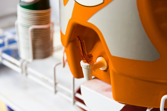 Orange water cooler used to hydrate athletes during sporting events
