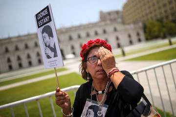 A woman covers her eye in reference to the protesters being blinded by rubber bullets and tear gas during an anti-government protests, in front of La Moneda Palace in Santiago