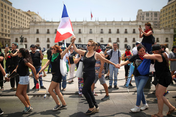Women dance during an anti-government protest, in front of La Moneda Palace in Santiago