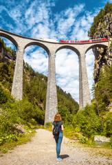 Landwasser Viaduct in summer, Filisur, Switzerland. Young woman looks at famous landmark of Swiss Alps. Red train runs on high railway bridge in Alpine mountains.