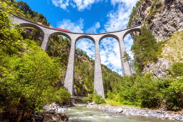 Landwasser Viaduct over river, Filisur, Switzerland. It is landmark of Swiss Alps. Red train runs on high railroad bridge in mountains. Scenic view of famous railway.