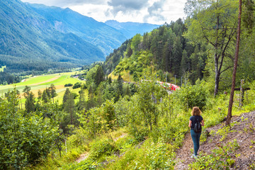 Alpine landscape in summer, Filisur, Switzerland. Young woman looks at red train of Bernina Express in forest. Adult girl travels in Alpine mountains.
