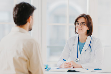 Heathcare, therapy session and assistance concept. Professional woman doctor speaks with male patient, gives consultancy and makes prescription, finds out symptoms of disease, provides help.